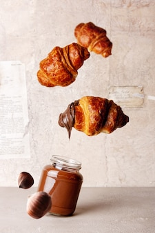 Schokoladenpaste, croissants auf vintage-papierhintergrund fliegendes essen