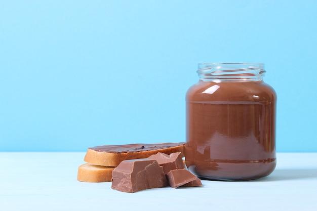 Schokoladenpaste im glas auf farbigem hintergrund