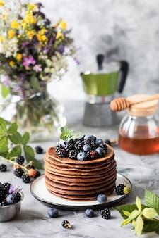Schokoladenpfannkuchen mit beeren und früchten mit honig, mit fliegendem puderzucker und einem strauß wilder blumen auf dem tisch. dunkel