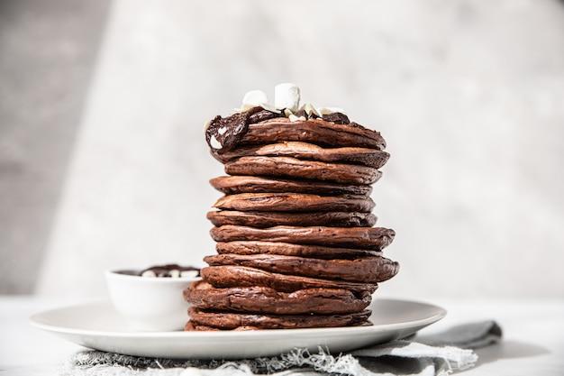 Schokoladenpfannkuchen mit geschmolzener schokolade, gemahlene mandeln und marshmallow