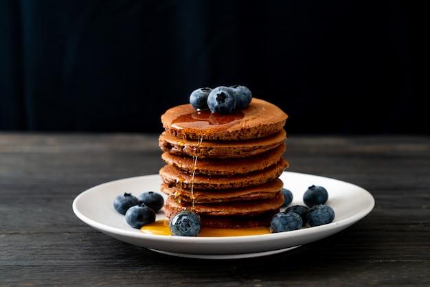 Schokoladenpfannkuchenstapel mit heidelbeere und honig auf teller
