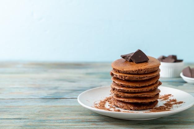Schokoladenpfannkuchenstapel mit schokoladenpulver