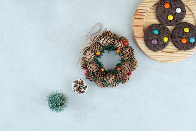 Schokoladenplätzchen auf holzteller mit weihnachtskranz.