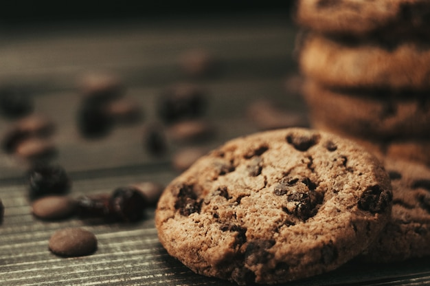 Schokoladenplätzchen auf holztisch. schokoladenstückchen und getrocknete früchte