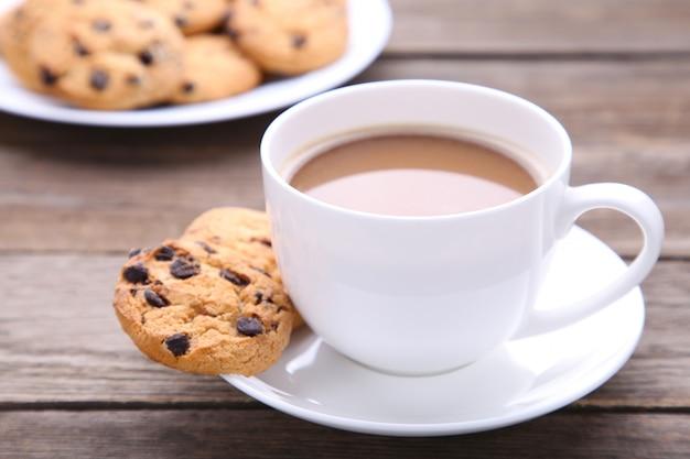 Schokoladenplätzchen auf platte und tasse kaffee auf grauem hintergrund