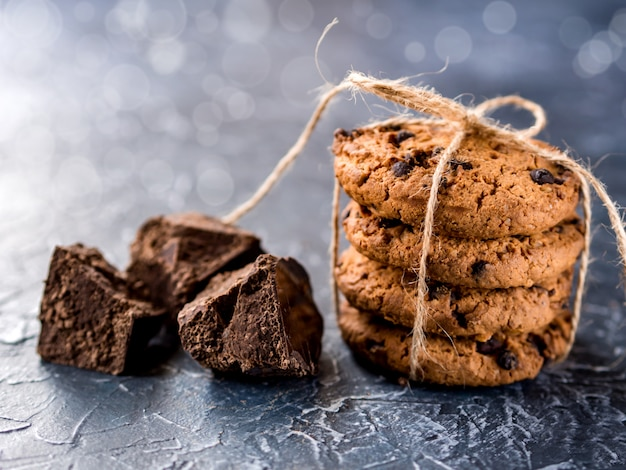 Schokoladenplätzchen, gestapelt und mit einem seil gebunden, stücke schwarze schokolade