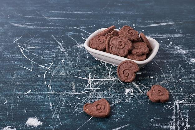 Schokoladenplätzchen in einer weißen keramikplatte auf blau.