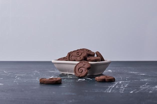 Schokoladenplätzchen in einer weißen keramikplatte.