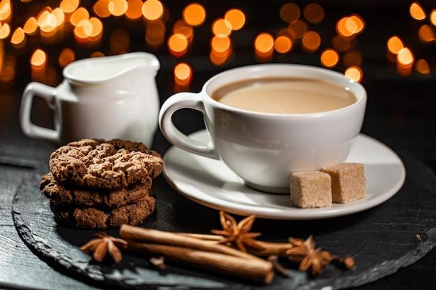 Schokoladenplätzchen, kaffee, gewürze auf unscharfen weihnachtslichtern.
