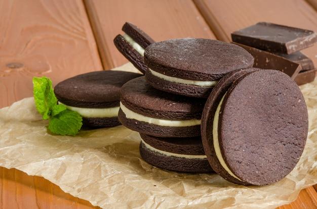 Schokoladenplätzchen mit buttercreme. selbst gemachte oreo-plätzchen mit einem glas milch.