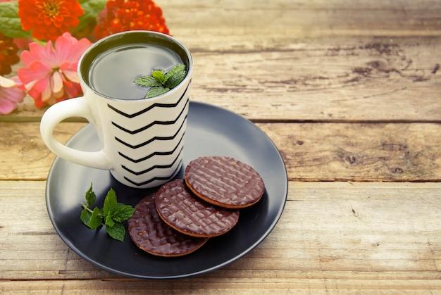 Schokoladenplätzchen mit einer tasse tee auf altem hölzernem hintergrund.