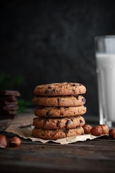 Schokoladenplätzchen mit glas milch auf holztisch.