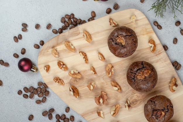 Schokoladenplätzchen mit walnüssen und kaffeebohnen mit weihnachtskugel auf holzbrett.