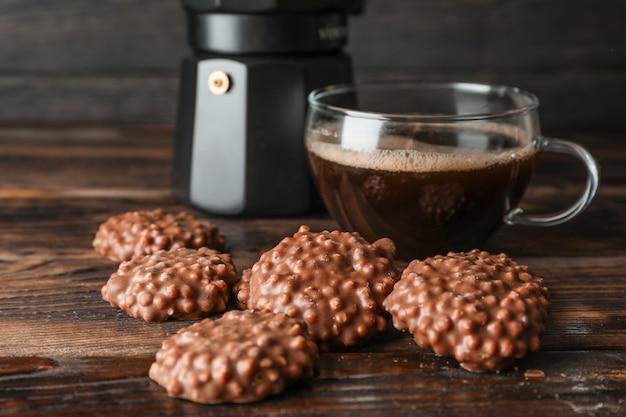 Schokoladenplätzchen und tasse kaffee auf holztisch gegen dunklen hintergrund