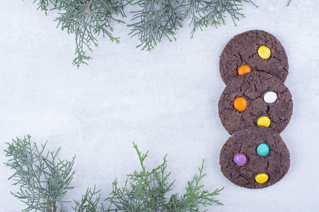 Schokoladenplätzchen verziert mit bunten bonbons.