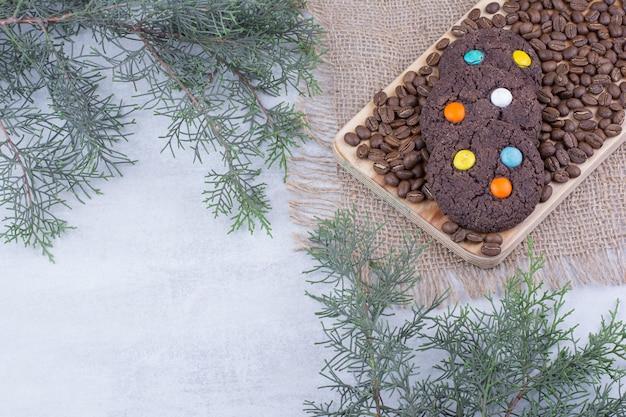 Schokoladenplätzchen verziert mit süßigkeiten und kaffeebohnen.