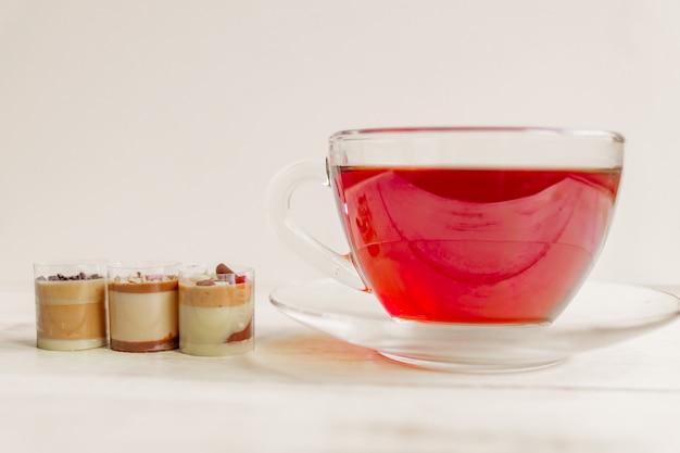 Schokoladenpraline canidies und tasse schwarzen tee. nahansicht.