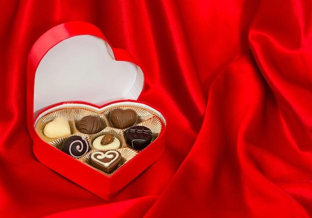 Schokoladenpralinen im goldenen herzformkasten über rotem seidenhintergrund. valentinstag geschenk. platz für deinen text