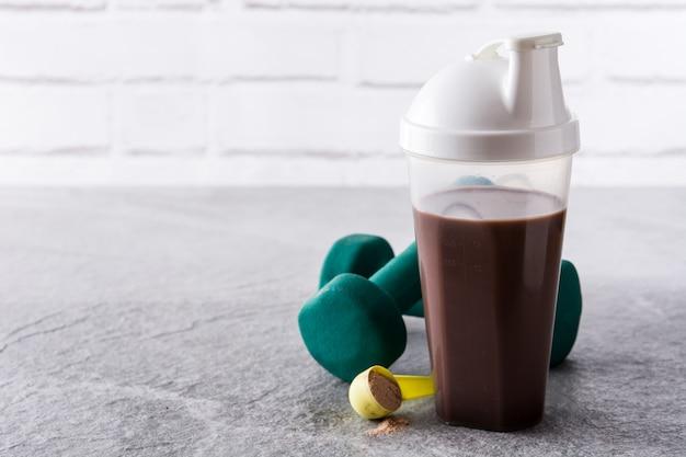 Schokoladenproteinshake und -dummköpfe auf grauem stein
