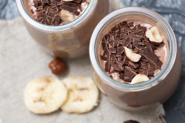 Schokoladenpudding mit chiasamen, bananen und nüssen, im glas