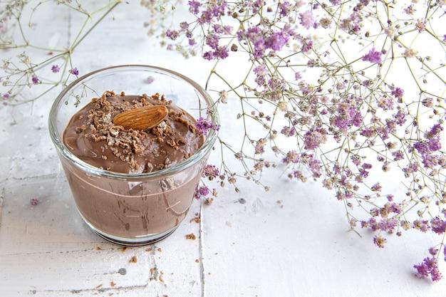 Schokoladenpudding mit mandeln verziert mit blumen