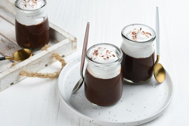 Schokoladenpudding mit schlagsahne und schokolade als topping in portionsgläsern