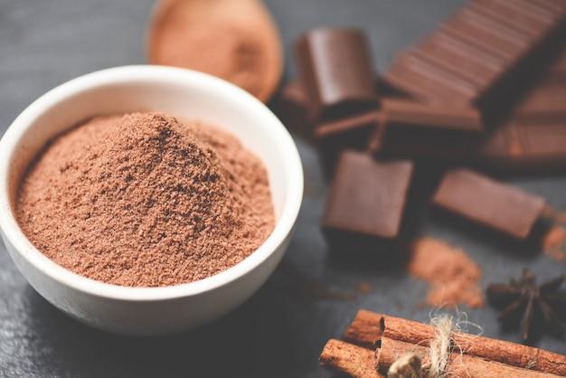 Schokoladenpulver auf schüssel- und süßigkeitssüßspeise für snackschokoladenriegel und -gewürz auf dunklem hintergrund, selektiver fokus