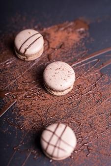 Schokoladenpulver und -sirup über den makronen auf schwarzem hintergrund