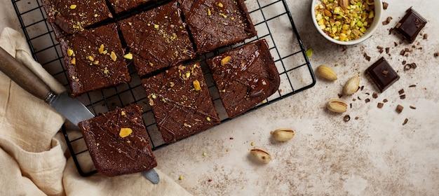 Schokoladenquadrate mit pistazien und erdbeeren auf einem metallständer auf einer hellen steinmauer, draufsicht, horizontale zusammensetzung. flach liegen.