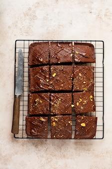 Schokoladenquadrate mit pistazien und erdbeeren auf einem metallständer auf einer hellen steinoberfläche, draufsicht, horizontale zusammensetzung. flach liegen.