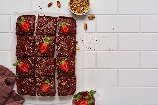 Schokoladenquadrate mit pistazien und erdbeeren auf weißem papier auf hellem hintergrund, draufsicht, horizontale zusammensetzung. flaches essen.
