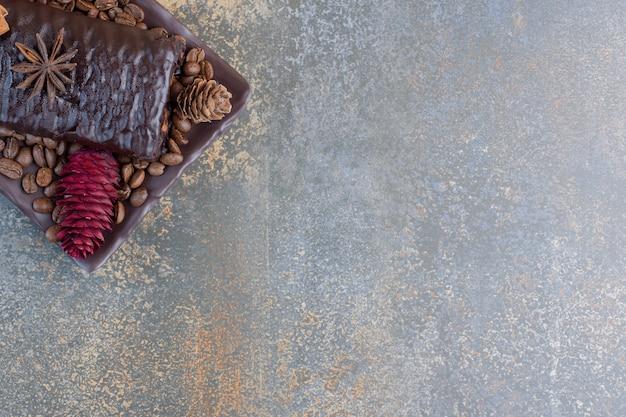 Schokoladenrolle mit kaffeebohnen und tannenzapfen. hochwertiges foto