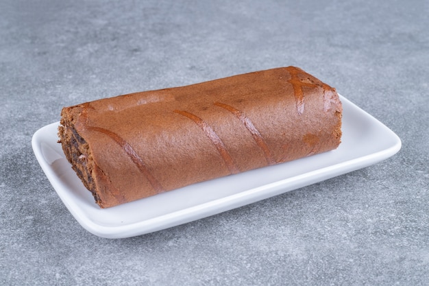 Schokoladenrollenkuchen auf weißem teller