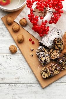Schokoladensalami mit nüssen und roten beeren auf holzhintergrund