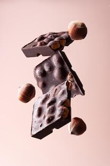 Schokoladenscheiben mit haselnüssen auf beigem hintergrund