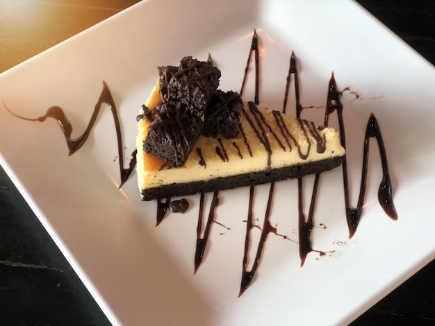 Schokoladenschokoladenkuchen, käsekuchen auf einer weißen platte, auf tisch servierfertig