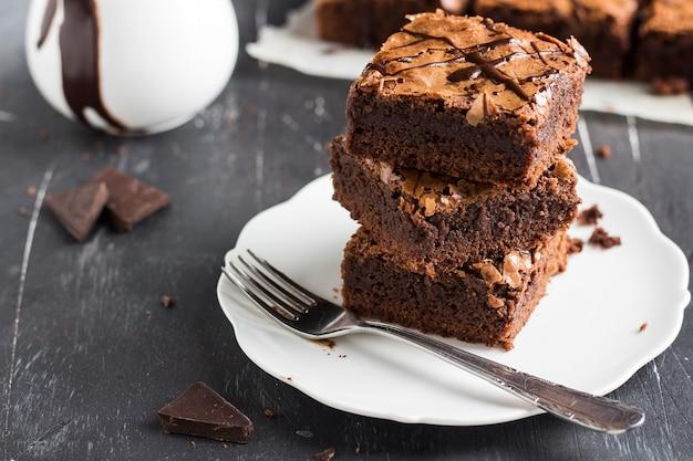 Schokoladenschokoladenkuchenkuchen-stückstapel auf selbst gemachtem gebäck der platte