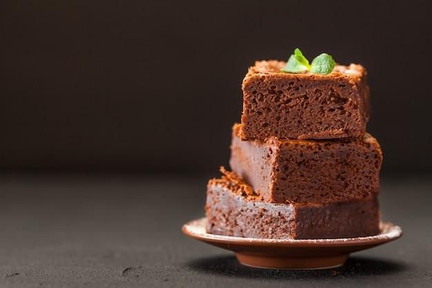 Schokoladenschokoladenkuchenquadratstücke im stapel auf weißer platte mit walnüssen