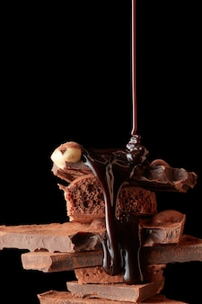 Schokoladensirup wird auf dunkle schokoladenstücke gegossen, die auf schwarz isoliert sind Premium Fotos