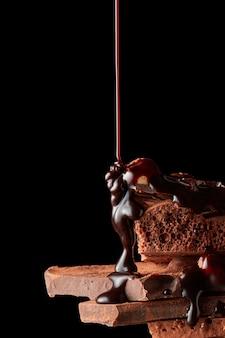Schokoladensirup wird auf dunkle schokoladenstücke gegossen, die auf schwarz isoliert sind