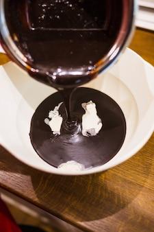 Schokoladensoße, die in schüssel fließt