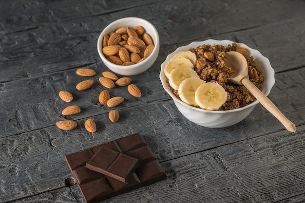 Schokoladenstückchen, mandeln und quinoa-brei mit banane auf einem holztisch. gesunde ernährung.