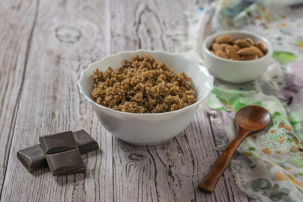Schokoladenstückchen, quinoa-brei, mandeln und ein holzlöffel auf dem tisch. gesunde ernährung.