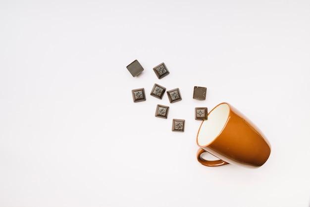 Schokoladenstücke, die vom becher auf weißem hintergrund fallen