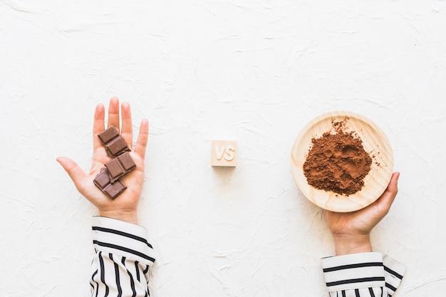 Schokoladenstücke gegen kakaopulver auf platte über weißem strukturiertem hintergrund