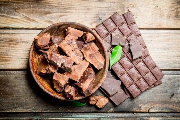 Schokoladenstücke in der schüssel. auf einem holztisch.