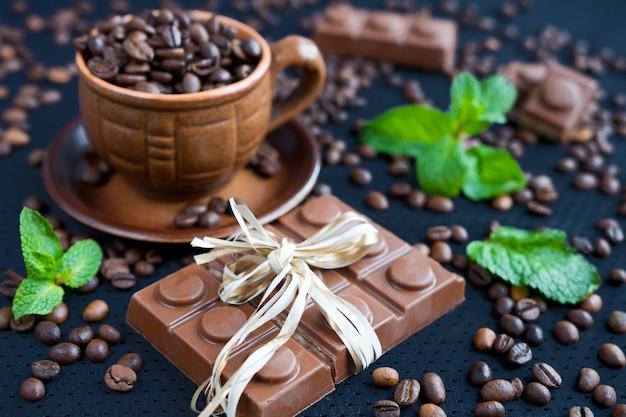 Schokoladenstücke mit tadellosen blättern auf schwarzem hintergrund