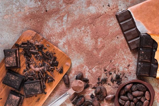 Schokoladenstücke, stangen- und kakaopulver und bohnen rollt auf unordentlicher tabelle