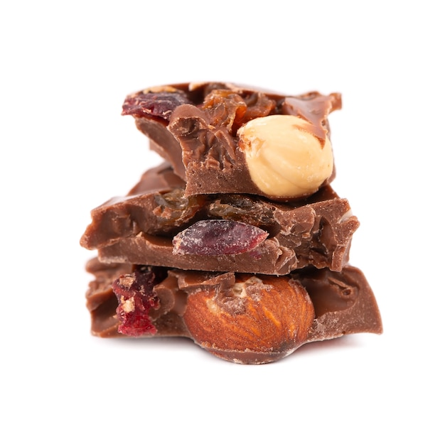 Schokoladenstücke stapeln mit nüssen und beeren, lokalisiert auf weißem hintergrund. nahansicht.