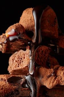 Schokoladenstücke und schokoladensirup lokalisiert auf einer schwarzen wand
